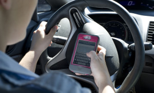 An Airman simulates texting and driving. Cell phone usage while driving is prohibited on Department of Defense installations. (U.S. Air Force photo/Airman 1st Class Nigel Sandridge)